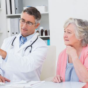 36413652 - male doctor showing reports to senior patient on computer in clinic